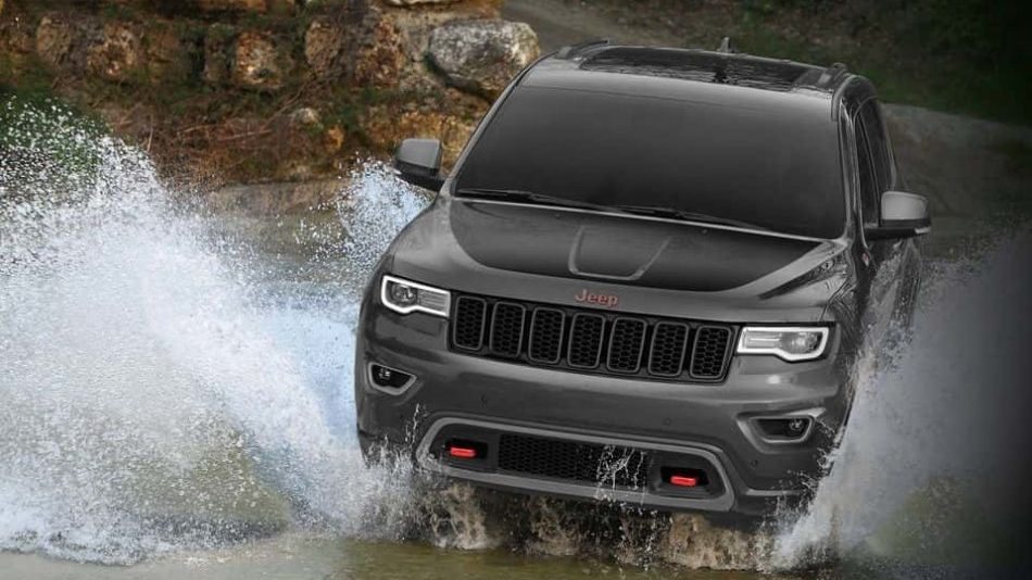 A 2018 Jeep Grand Cherokee effortlessly fords a river in the rugged back country