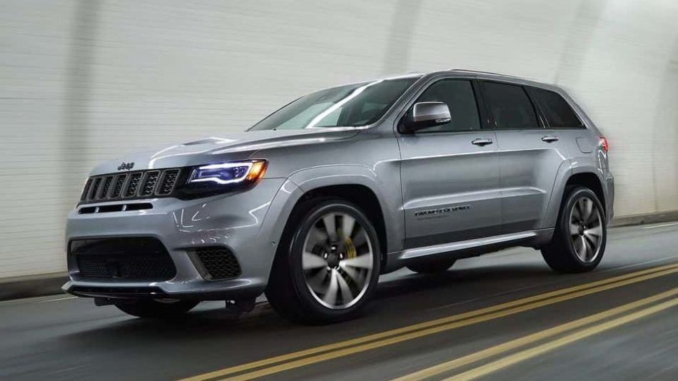 A silver 2018 Jeep Grand Cherokee soars through a city underpass
