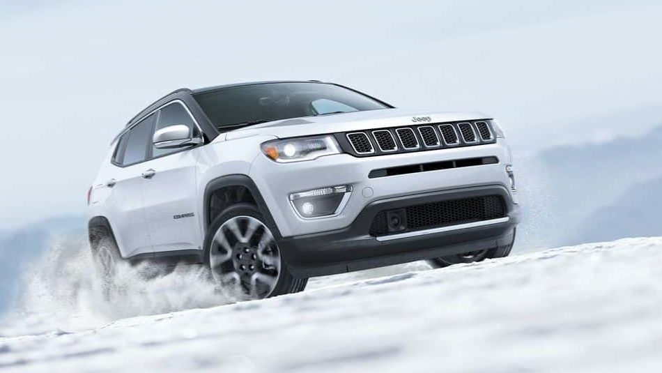 A white 2018 Jeep Compass masters a snowy terrain