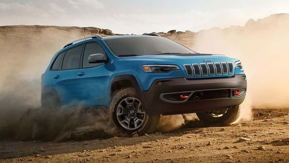A blue 2019 Jeep Cherokee kicks up a cloud of dust as it goes off-road