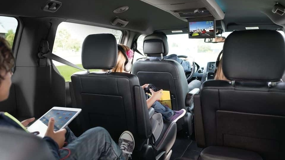A family of five makes use of the spacious interior of the 2018 Dodge Grand Caravan, with the kids playing games on devices in the back