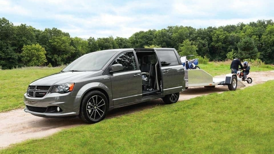 A silver 2018 Dodge Grand Caravan with side door open, and a trailer hitched to the back