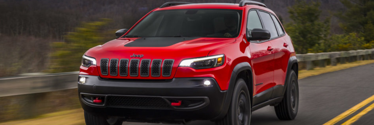 Red Jeep Cherokee Trailhawk driving on the road.