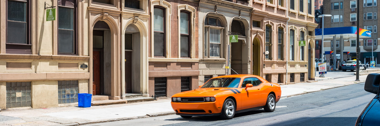Dodge Challenger parked in front of townhouses