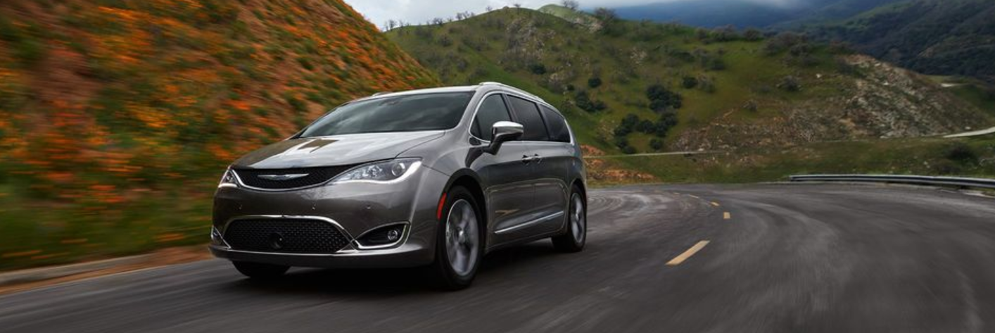 Chrysler Pacifica driving on winding country road beside a hill