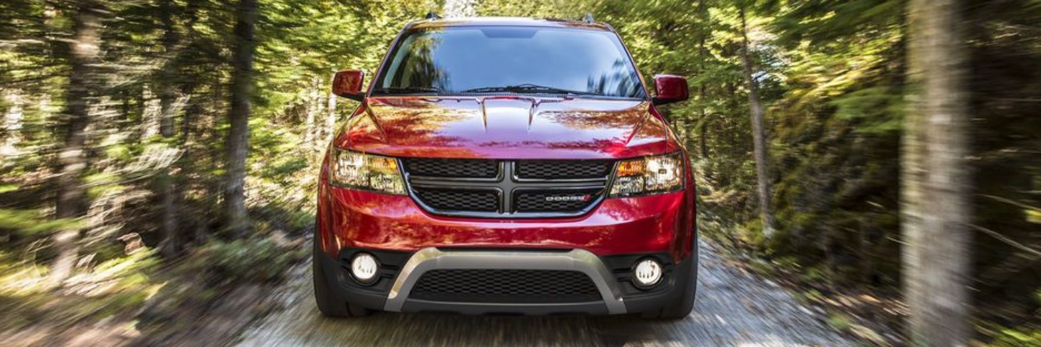 2018 Dodge Journey driving through a tree-surrounded road