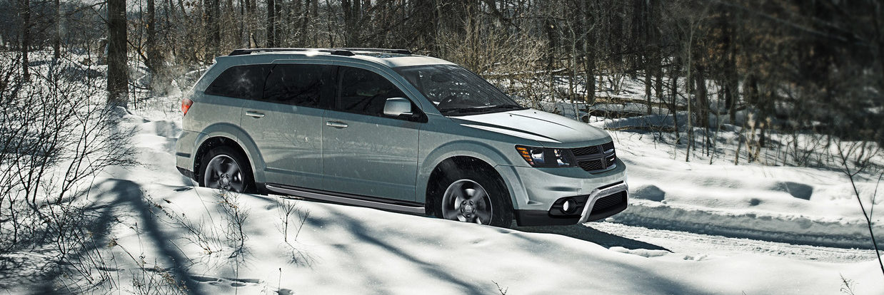 Dodge Journey driving in the snow through some trees