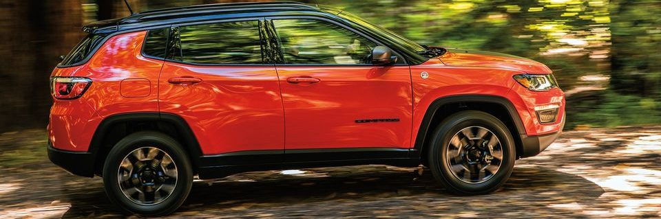 Orange Jeep Compass in forest