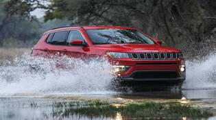 Red Jeep Compass driving through water