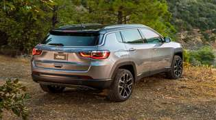 Rear shot of silver Jeep Compass in forest