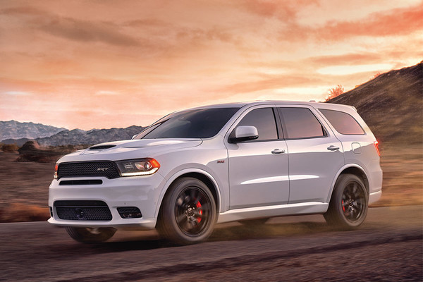 Dodge Durango in White driving on back road during sunrise