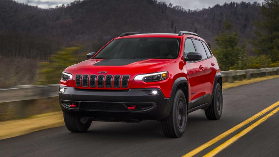 Red Jeep Cherokee Trailhawk driving down highway