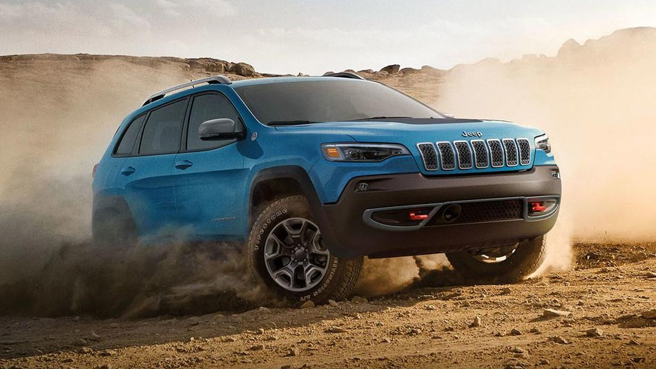 Blue Jeep Cherokee raising dust from dirt road