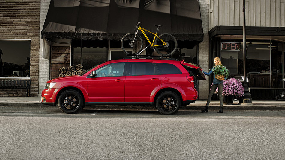 2019 Dodge Journey with bike rack accessory parked along sidewalk