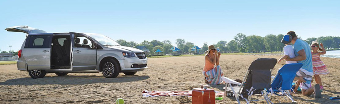 2019 Dodge Grand Caravan parked at a beach with family taking a photo in the foreground