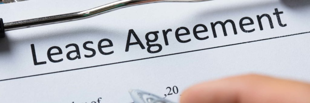 "A person gets set to sign a contract labeled ""Lease Agreement"""