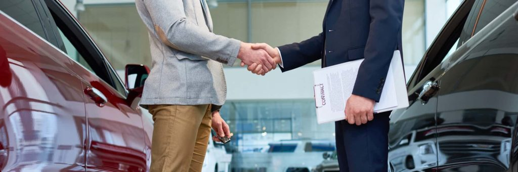 Two well-dressed men share a handshake in between two shiny new vehicles, one of the men carrying a contact for the sale of a vehicle