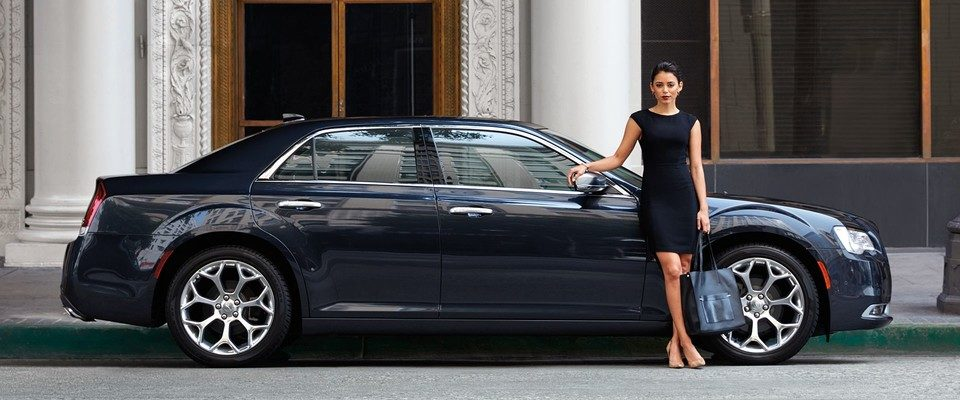 woman in a black dress standing outside of a chrysler 300