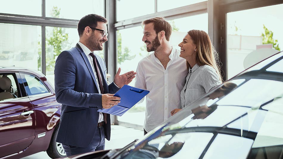 Sales person assisting a couple with car shopping