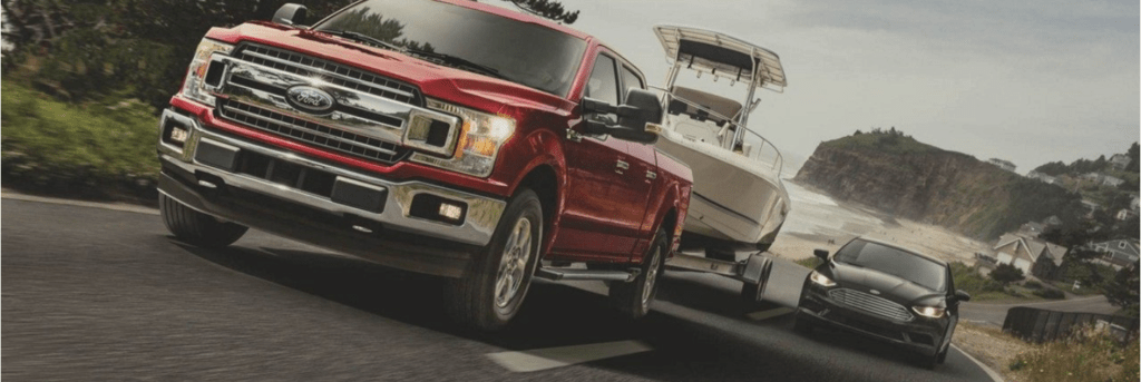 Red Ford F-150 towing a boat behind it