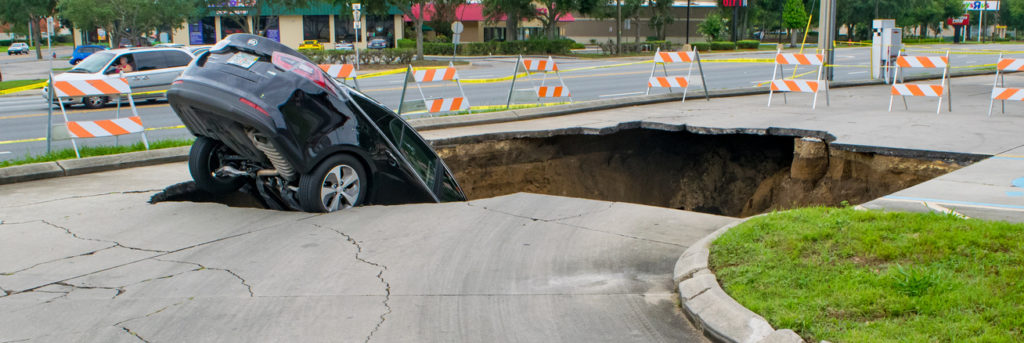 Ocala, Florida, USA - June 11, 2017: A large sinkhole opens in a parking area and swallows a car that teeters on the edge.