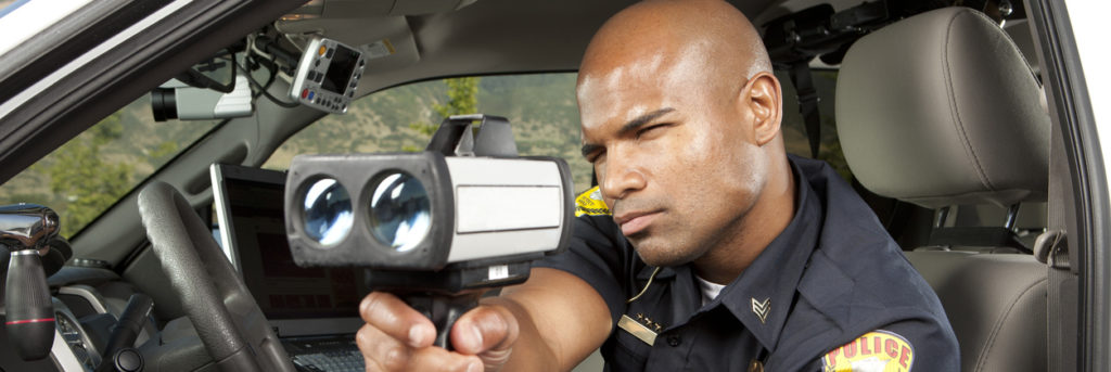 Police Officer checking vehicle speed with radar gun. This stock image has a horizontal composition. Arm Badge Create by me, Gold Chest Emblem Custom Ordered Generic