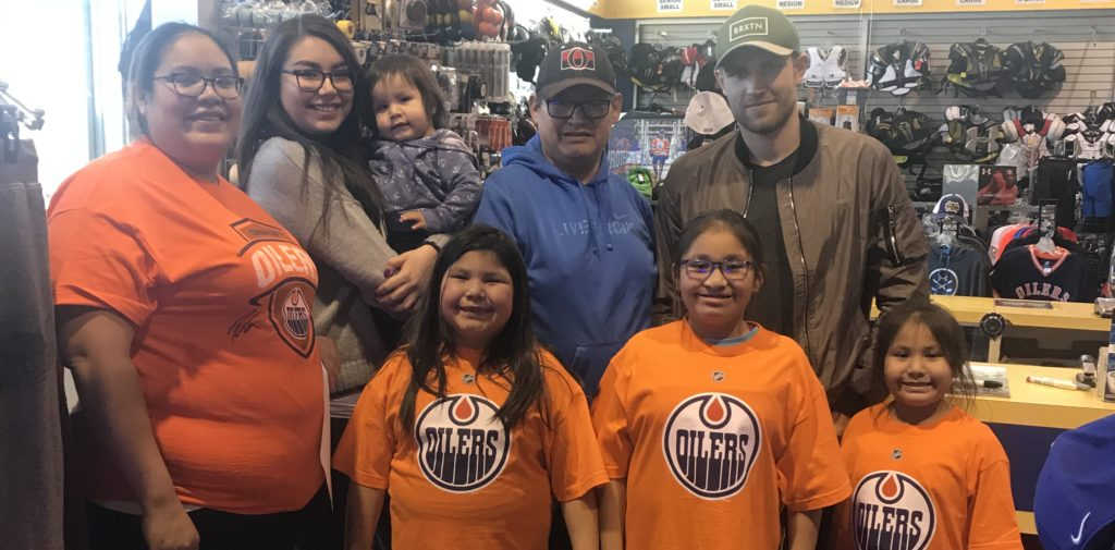 Leon Draisaitl posing with the Gear for a Year winner and her family
