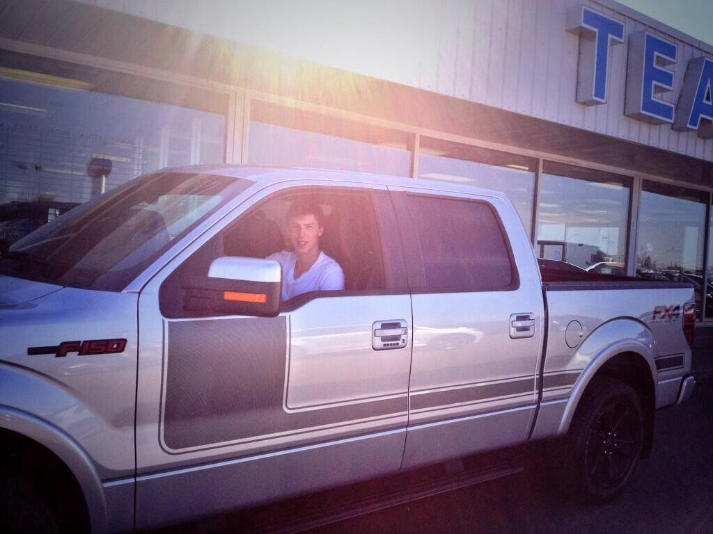 Ryan Nugent Hopkins driving a customized grey F-150 in front of Team Ford