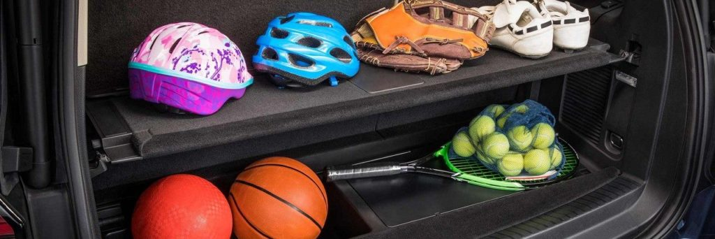 The Advanced Cargo System for the Ford Expedition carrying pink and blue bike helmets on the top shelf and two orange balls and a tennis racket on the second shelf