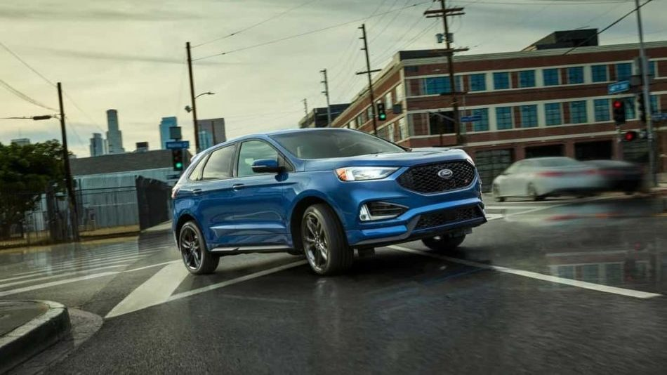 2019 Edge ST Shown in Ford Performance Blue turning on the street in the rain