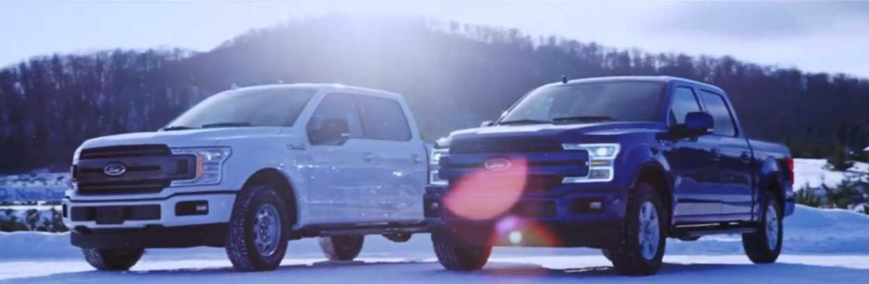 Two Ford F-150s. one in black and one in white, parked on snow with a mountain in the background with some lensflare