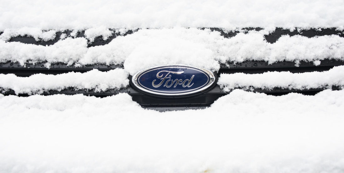 Ford front grille and logo with some snow.