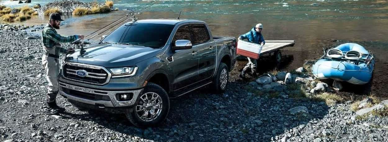 Two fishermen unload a raft and a cooler 2019 Ford Ranger LARIAT Chrome 4x4 SuperCrew in Magnetic that's parked beside a river