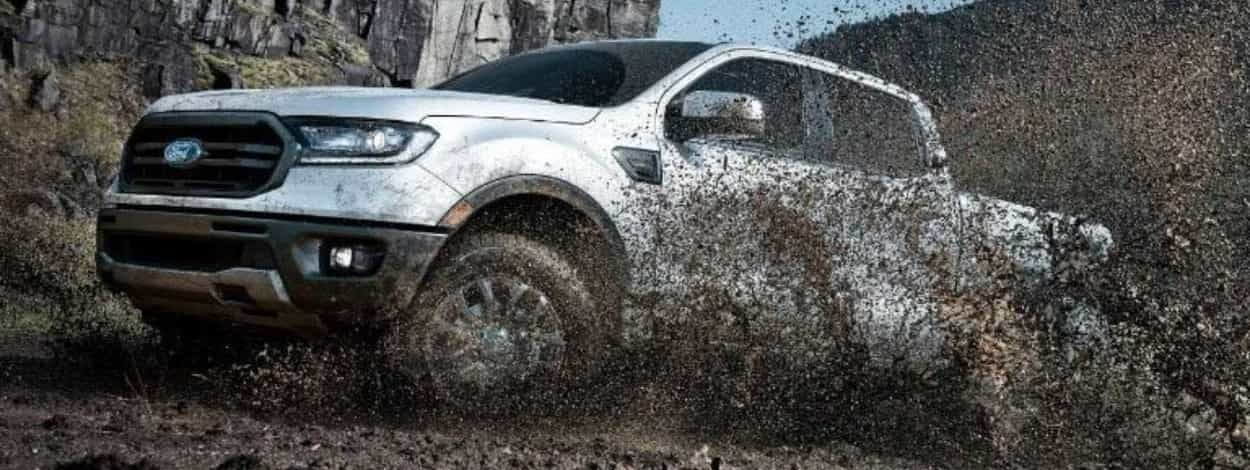 A Ford Ranger splashing through a muddy road