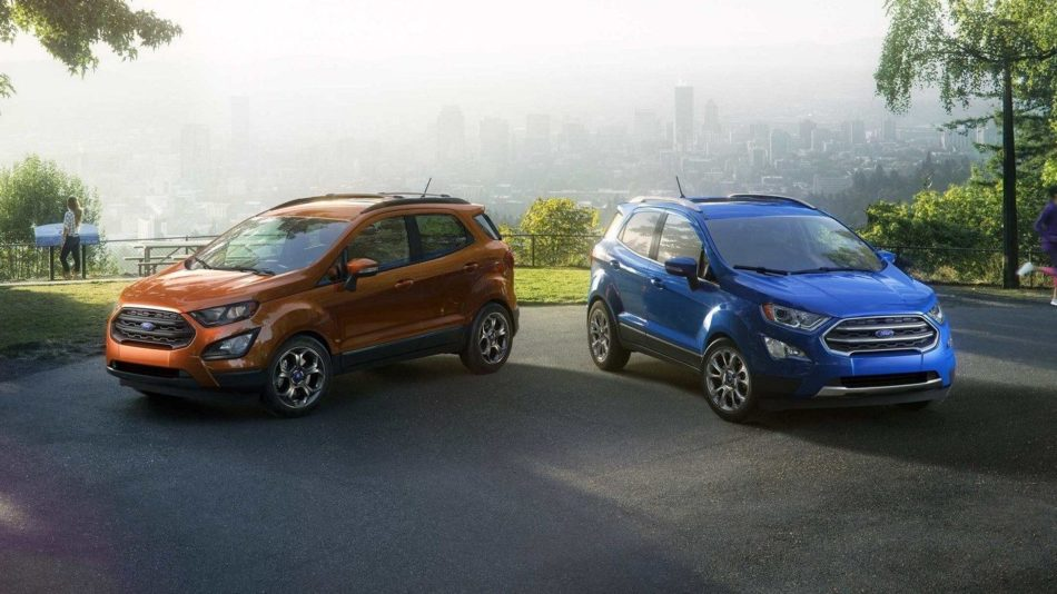 Two Ford Ecosports in orange and blue parked with a backdrop of a view from the hills