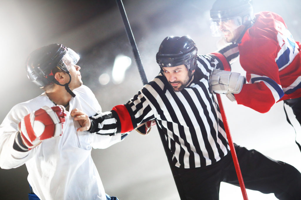 Two male ice hockey players in a fight during game. They are about to throw some punches. Referee is trying to stop them. Wearing white and red jerseys. Common scene in hockey game.