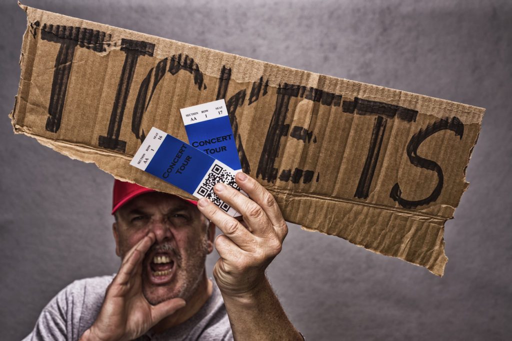 A shady character scalping a pair of concert tickets, yelling while holding a cardboard sign and wearing a red baseball hat. The concert tickets have a QR Code on them.