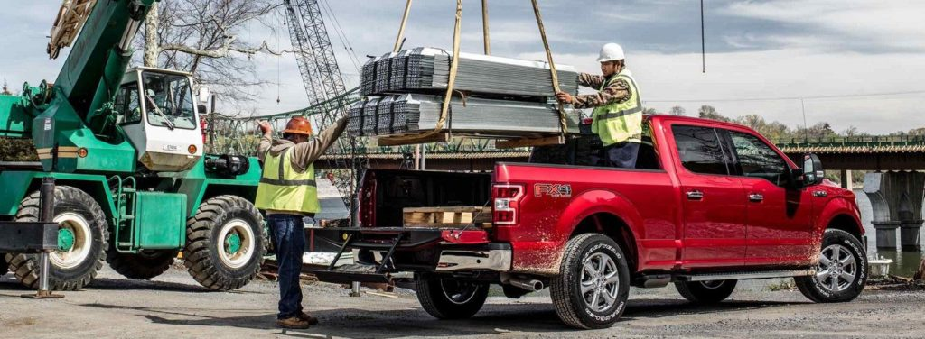 F-150 XLT in Ruby Red with XTR package loading plywood into the truck bed