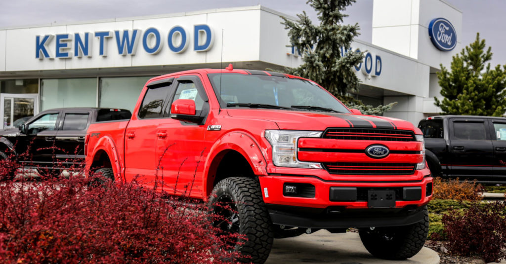 Ford F-150 with custom red paint parked in front of the Kentwood Ford sign