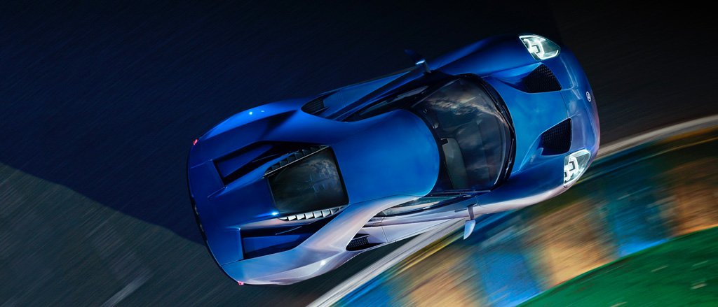 2019 Ford G T in Liquid Blue driving forward on racetrack at night
