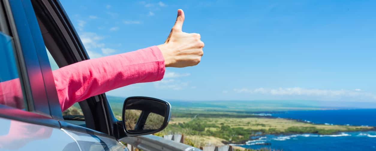 Female traveler on the road holding thumbs up.