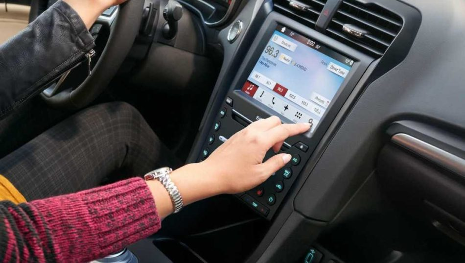 A hadn reaching out to use the Ford Fusion's SYNC 3 touchscreen system