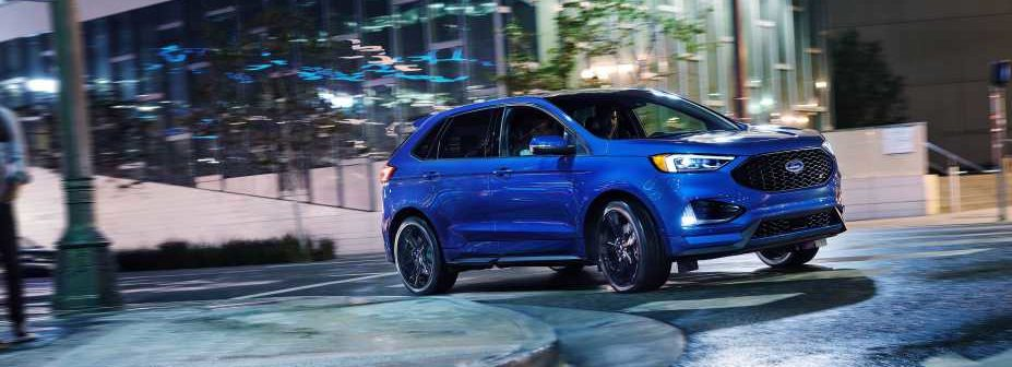 2019 Ford Edge ST in performance blue driving around a corner in the city