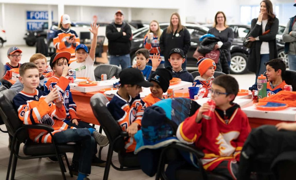 Young hockey players in Oilers jerseys (one kid in a Calgary Flames jersey) eating pizza while they're parents watch with envy