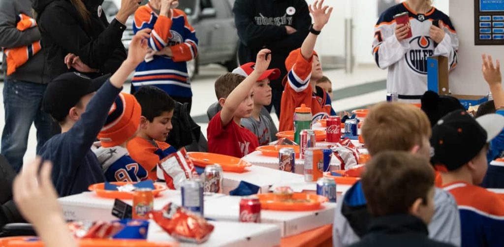 Young hockey players in Oilers jerseys raising their hands to ask Lucic a question