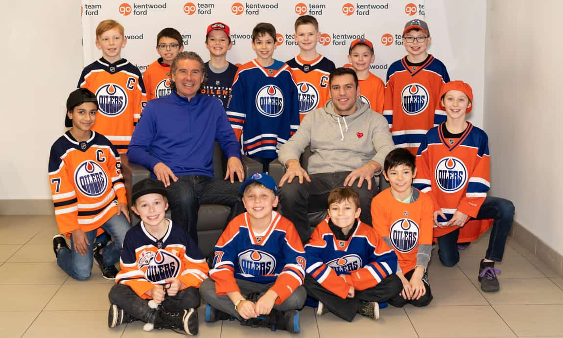 Milan Lucic and Gene Principe sitting in chairs posing for pictures with the Atom Millwoods Bruins minor league hockey team