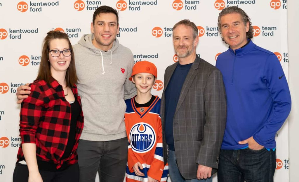 Milan Lucic, Gene Principe, Ashley Roy, and two other people posing for a picture