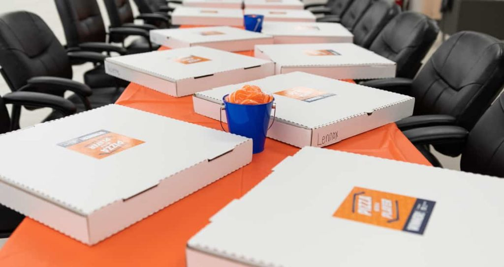 "Pizza boxes with the ""Pizza with a Player"" logo layed out on an orange table"