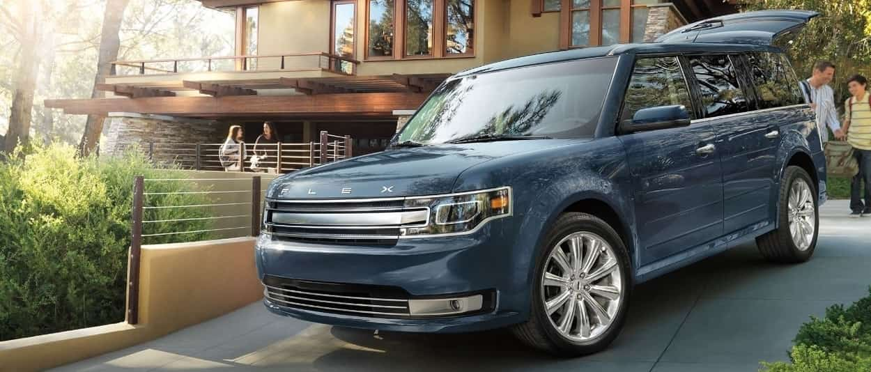 The 2019 Ford Flex Limited in Navy Blue parked on a driveway of a nice modern house