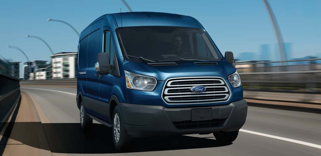 2019 Ford Transit in Blue Jean Metallic paint driving on a highway road